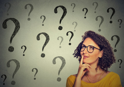 Thinking young business woman in glasses looking up at many question marks