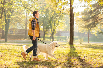Young guy walking his dog in a park