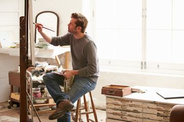 Male Artist Working On Painting In Studio Wall mural