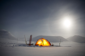 Camping in the Wintertime with Moon and Halo at Night
