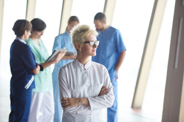 female doctor with glasses and blonde hairstyle standing in fron