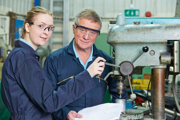 Engineer Showing Female Apprentice How To Use Drill