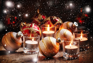 Christmas balls, burning candles on the old wooden background, d