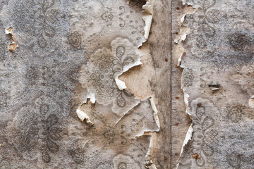 Aged room wall background with torn vintage wallpaper.