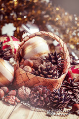 Wicker basket with fir cones, nuts, Christmas balls, tinsel and