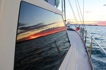 Der Sonnenuntergang spiegelt sich im Bootsfenster
