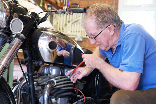 Senior Man Working On Vintage Motorcycle In Garage