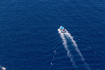 Ship navigates into beautiful blue water near Santorini island,