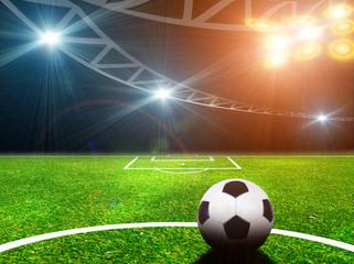 Soccer ball on green stadium, arena in night illuminated