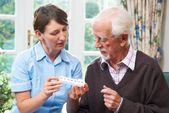 Carer Helping Senior Man With Medication