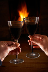 Couple With Glass Of Wine Relaxing By Fire