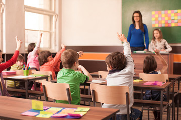 Children in elementary school are raised hand in clasroom