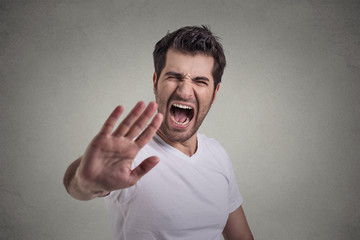 portrait of young angry man screaming to stop stay away