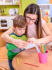 kindergarten teacher and cute boy on creative activities