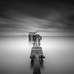 Fine art image of wooden fishing jetty at beach in black and white.Long exposure shot with motion blur.