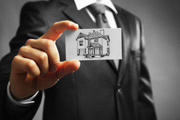 Businessman with house picture, concept real estate