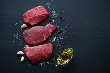 Raw marbled meat steaks with seasonings, black wooden surface