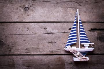 Decorative sailing boat on  vintage wooden background.