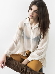 Pretty and fashionable girl portrait sitting and looking