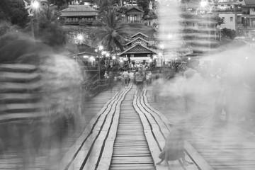 Black and white blur image of Traveler crossing bamboo bridge or Mon Bridge in Sangklaburi. Kanchanaburi, Thailand