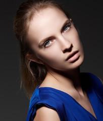 Portrait of blond woman in blue dress.