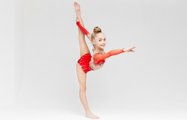 Little girl in red dress doing standing split.