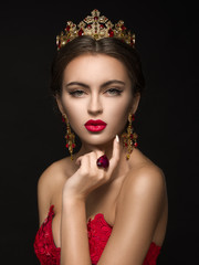 Beautiful girl in a golden crown and earrings on a dark backgrou