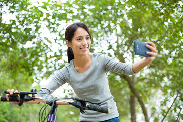 Asian woman take selfie with her bicycle