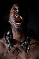 Bare chested black man, screaming out and holding a large heavy chain around his neck.