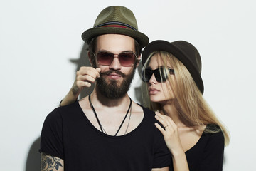 beautiful happy couple in hat wearing trendy glasses together