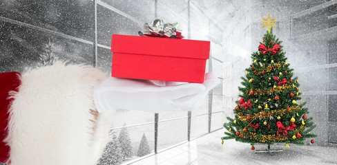Composite image of hand of santa claus holding a gift