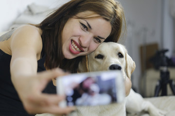 Young Caucasian girl taking a selfie with labrador dog at home