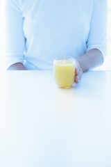 Cropped view of a woman holding a chilled glass of fresh orange juice on a white counter.