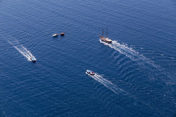 Yacht navigates into beautiful blue water near Santorini island,