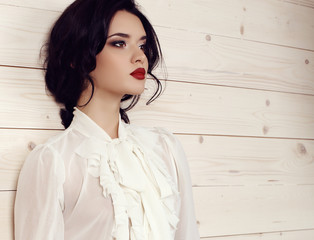 sensual woman with dark hair in elegant clothes posing at studio