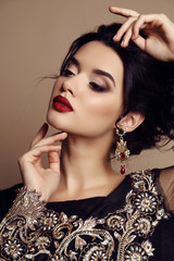 gorgeous young woman with dark hair in luxurious dress