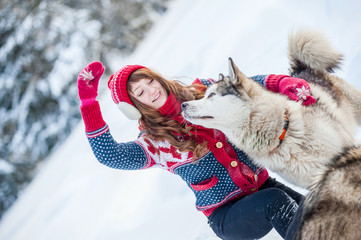Young girl playing with the dog husky in the winter