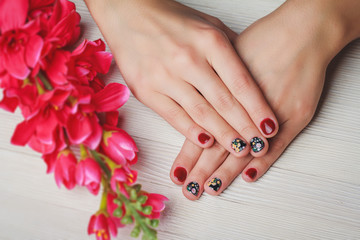 Red nail art with printed flowers on wooden background