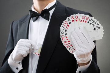 Wall Mural - Magician Showing Fanned Out Cards Against Gray Background