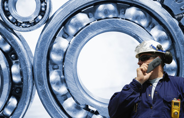Wall Mural - industry worker, engineer with giant ball-bearings in background