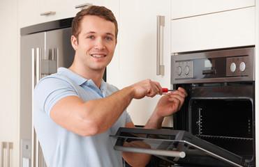 Engineer Reapiring Domestic Oven In Kitchen