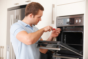 Man Repairing Domestic Oven In Kitchen