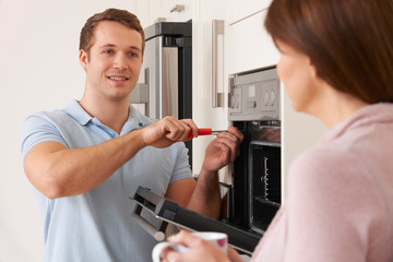 Engineer Giving Advice To Woman On Kitchen Repair