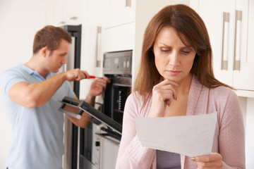 Woman Looking Concerned At Bill For Repair Of Kitchen Appliance