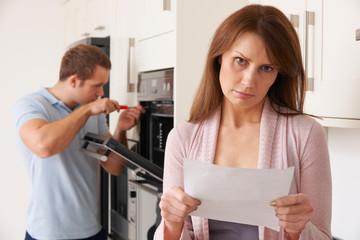 Woman Looking Concerned At Domestic Repair Bill