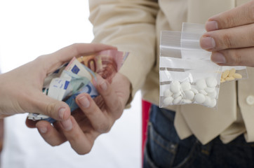 Closeup of drug trading with money and pills.