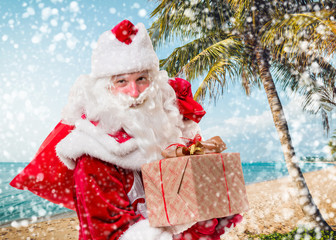 Santa Claus with a gifts on the beach