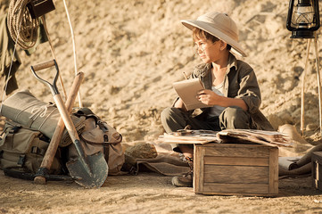 Boy archaeologist take notes in a notebook on the excavations conducted
