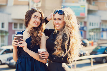 Lifestyle portrait of two best friends girls spending time in the center of the city at nice summer day, trendy fashion looks