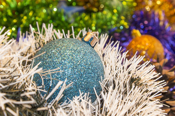 Background for New Year's and Christmas cards. Celebratory  holiday bright rainbow decorations for Christmas trees or pine. Focus on  blue toy